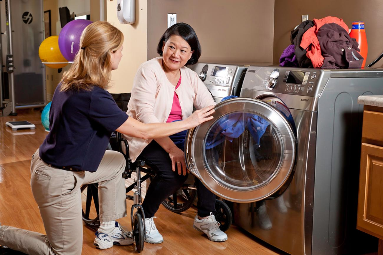 Occupational Therapist helping patient load a washing machine