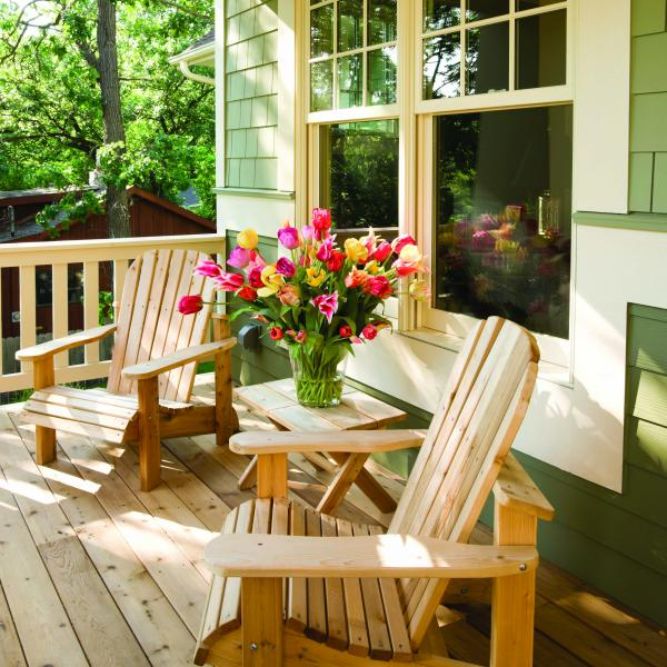 Photo of a residential deck with two deck chairs and flowers.